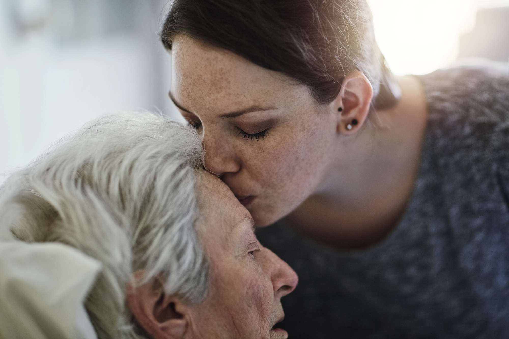 Woman kissing the top of grandmother's head