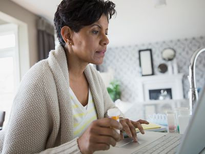Woman with prescription bottle of thyroid making sure she isn't making mistakes