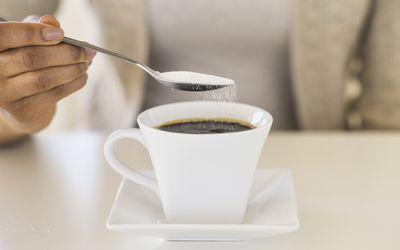 close up of woman sweetening coffee