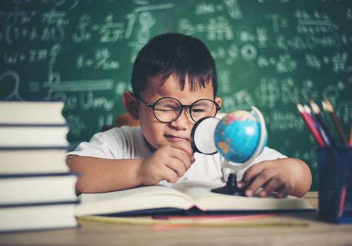 young asian Boy Studying At Table Against Blackboard