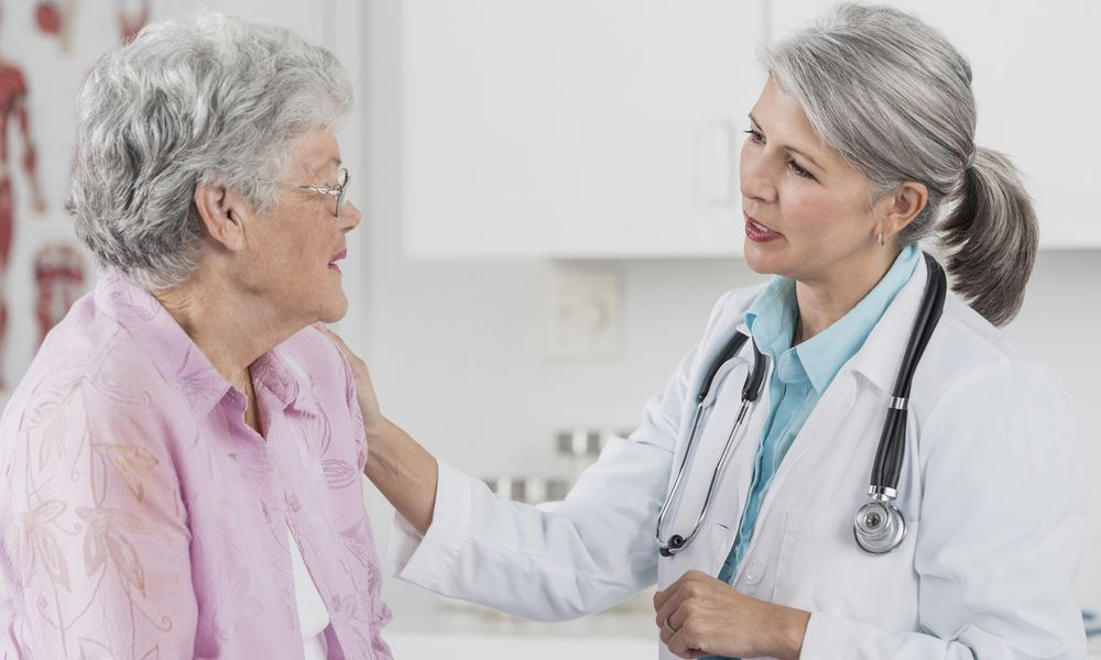 An elderly patient talks with her doctor.