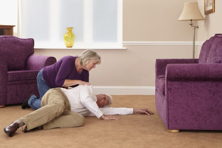 Woman bending over elderly man who has fallen