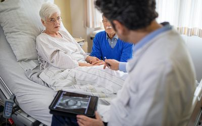 Doctor explaining the knee replacement treatment to senior patient