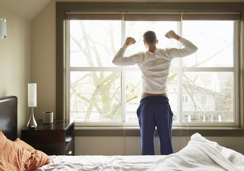 Man stretching in front of a window in his bedroom