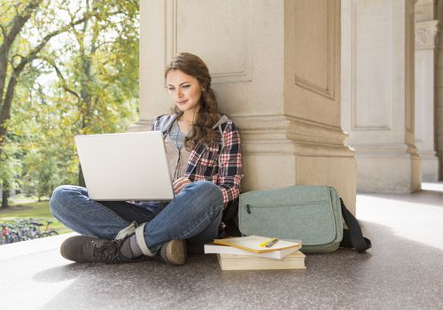 young woman sitting outside by a pillar with a computer