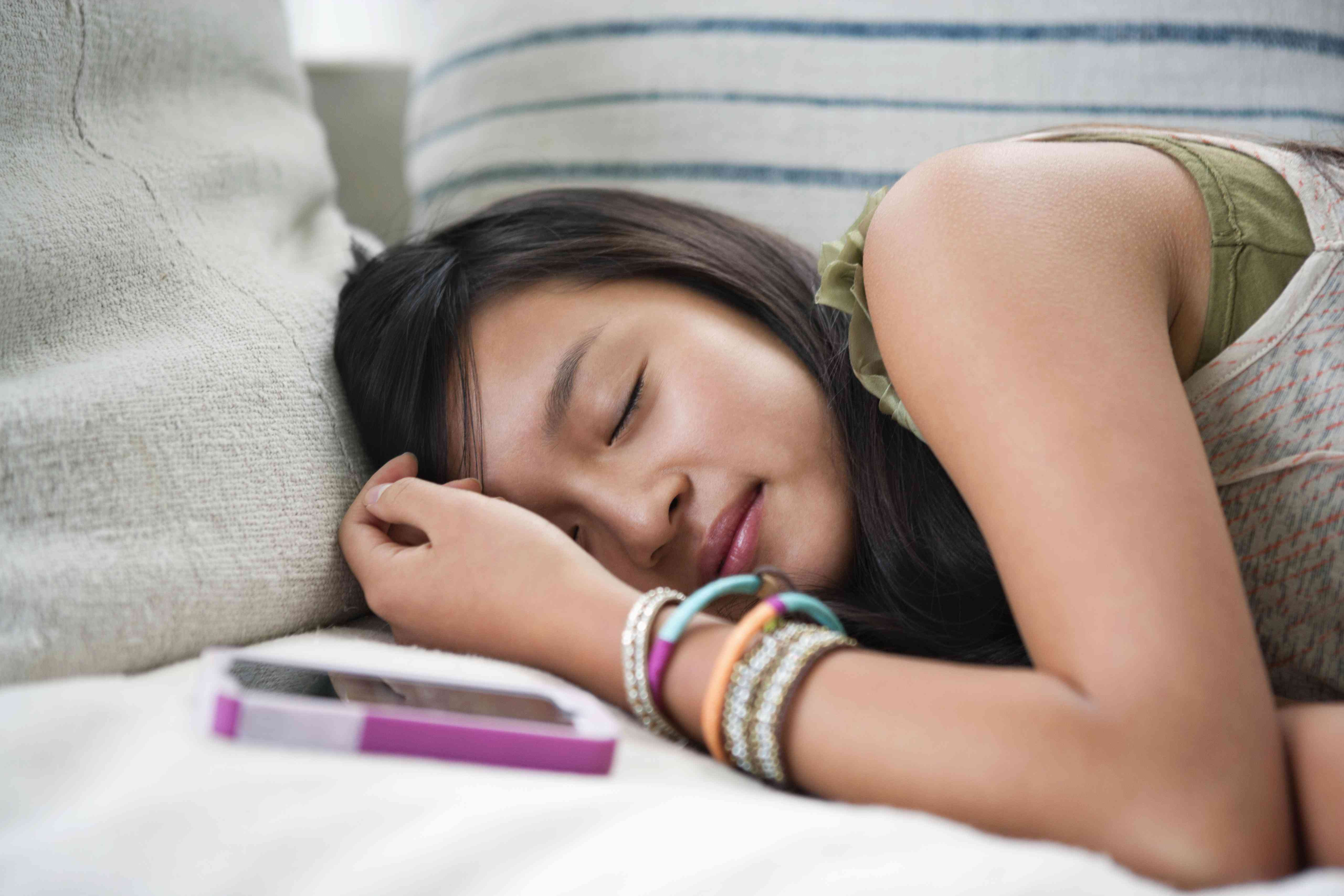 A teenage girl asleep on the couch
