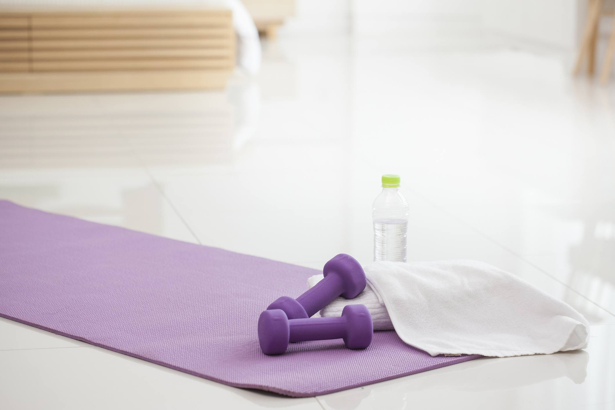 Dumbells sit on a yoga mat along with a rolled towel and a water bottle.