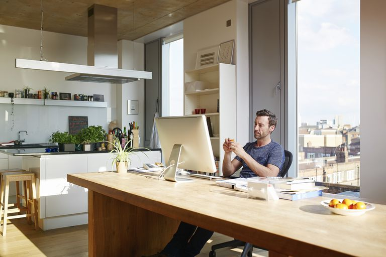 Man sits in front of computer at a home workspace