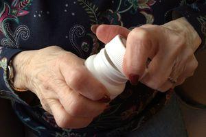 An older woman with arthritis opening a pill bottle