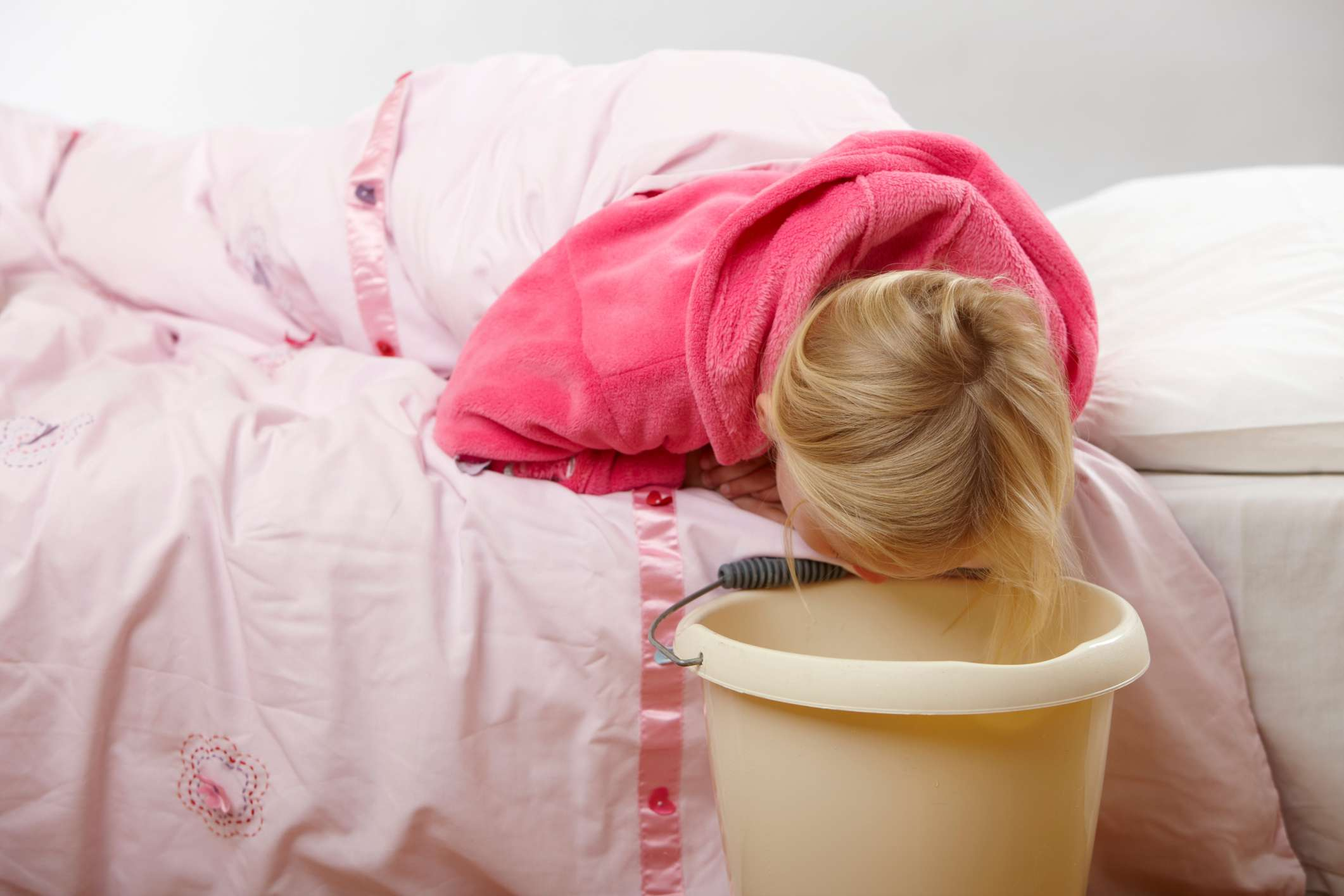 Woman vomiting into bucket from bed