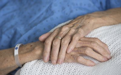 Closeup of crossed hands of a hospital patient