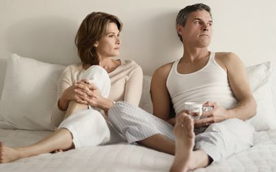 couple looking serious in bed