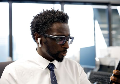 Business person uses Bluetooth earbuds