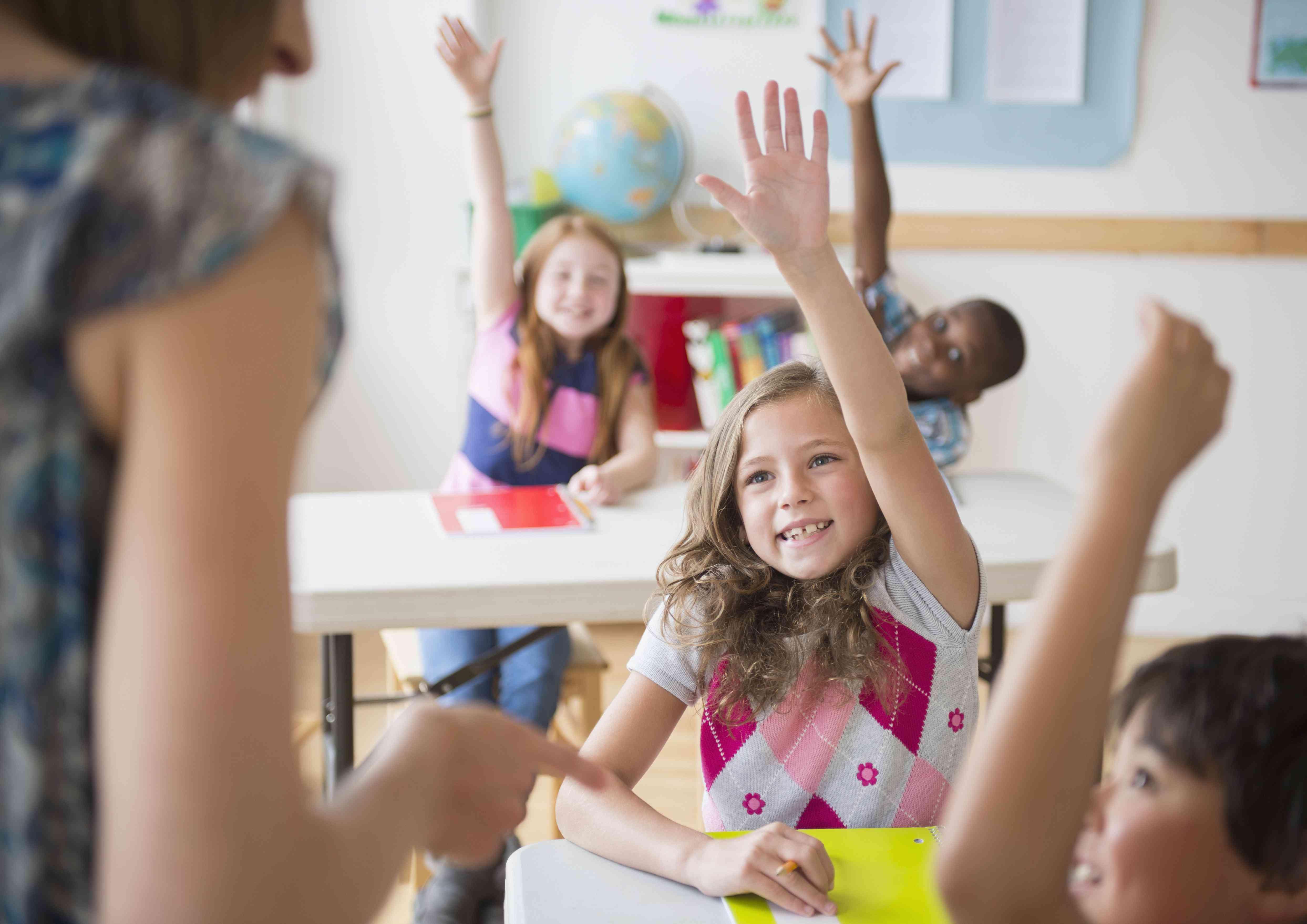 Children raising their hands in a classroom