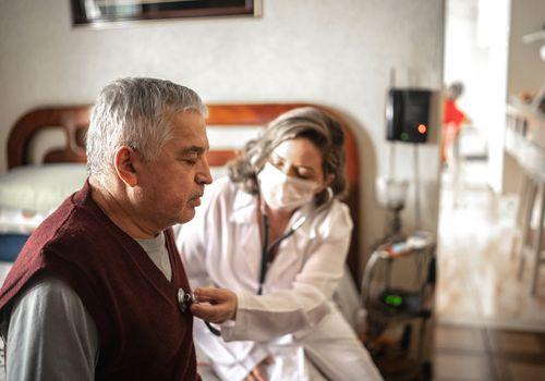 Doctor checking an older man's heart beat.