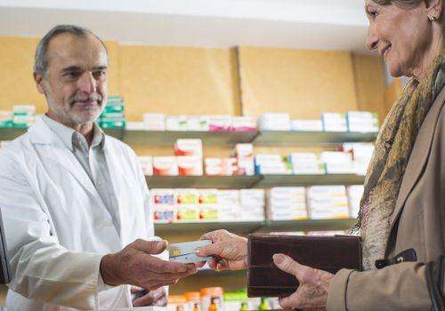 senior woman handing card to pharmacist