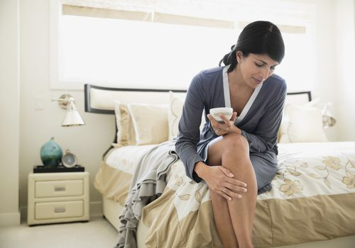 Woman sitting on her bed with a cup of tea rubbing her leg
