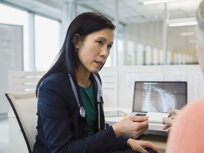 Doctor giving business card to patient in clinic office