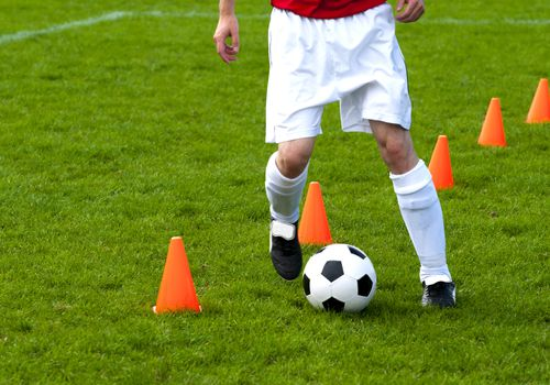 man from waist down playing soccer on field with cones