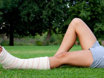 Girl with plaster on leg lying on grass