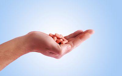 Hand holding HIV pills
