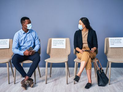 Two people wearing masks and sitting on chairs, with a chair between them in order to observe physical distancing.