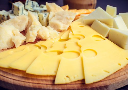 plate of different sliced and cubed cheeses