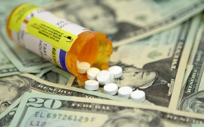 pills spilling out against cash