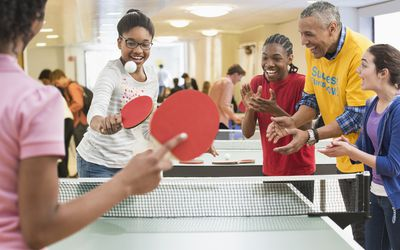A group of kids and adults playing ping pong