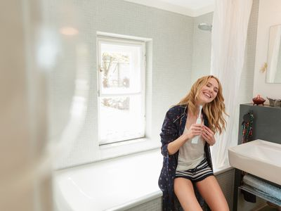 Woman in bathroom holding electric toothbrush smiling