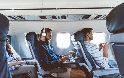 Male passenger using laptop during flight
