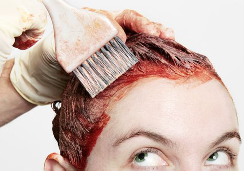 Woman getting her hair dyed red