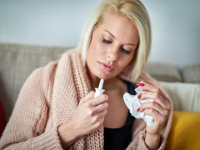 Blonde woman with flu using nasal spray