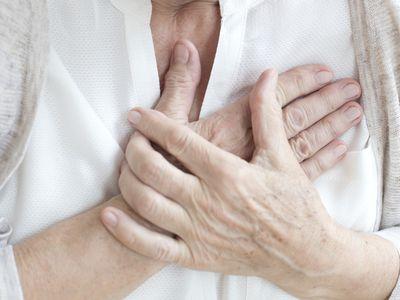 Senior woman holding chest