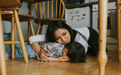 Woman comforts child under a table