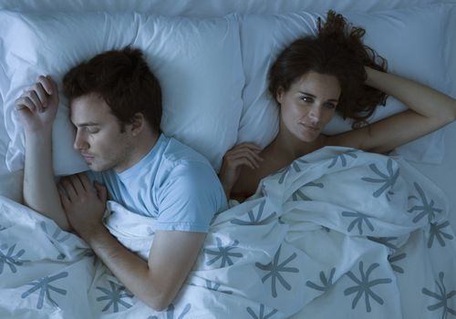 couple in a bed, man is sleeping woman is awake