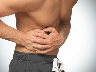 man holding his ribs appearing to be in pain