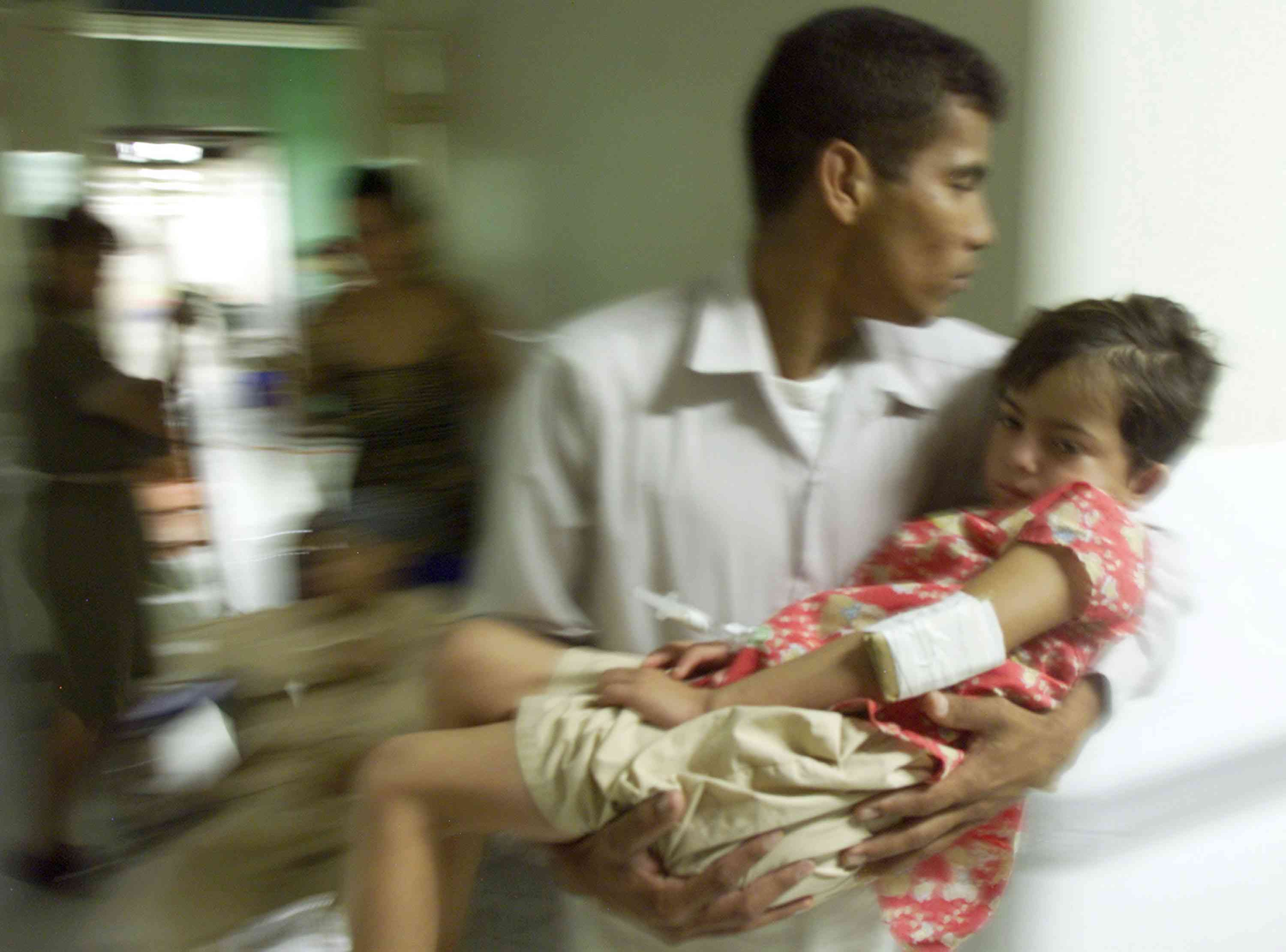 A child with Dengue fever during a 2002 outbreak in Honduras being carried by an adult man
