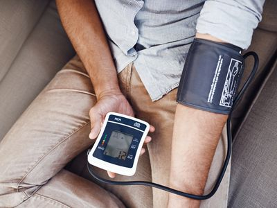 Top-down view of a person with a blood pressure cuff on their arm and holding the monitor with their free hand.