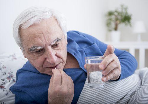 Senior man taking medication in bed