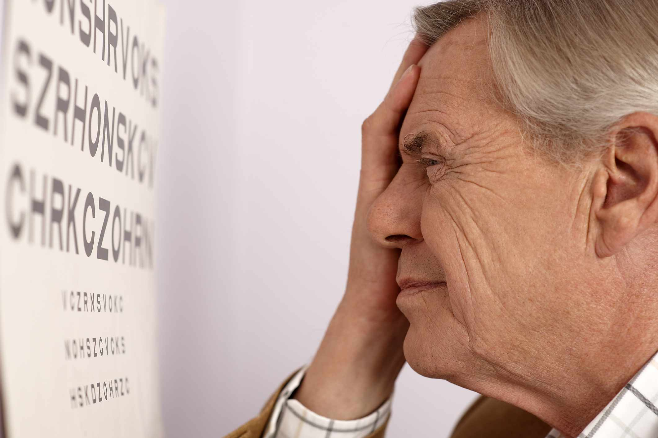Man looking at eye chart with one eye covered by hand