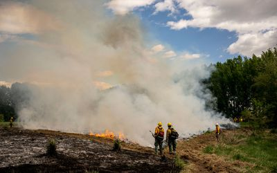 Volunteer firefighters manage a live burn during a wildfire training course on May 8, 2021 in Brewster, Washington