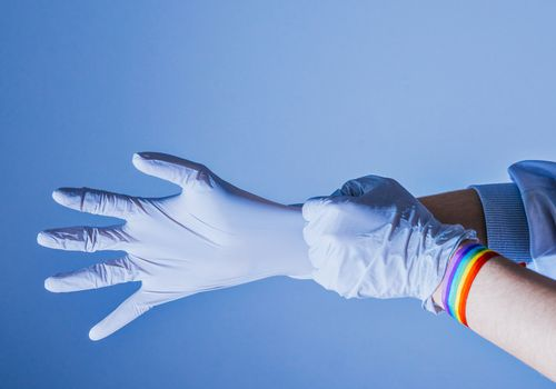 Nurse putting on latex gloves. On her wrist she wears a bracelet with the lgtb flag. Concept of health and prevention. - stock photo
