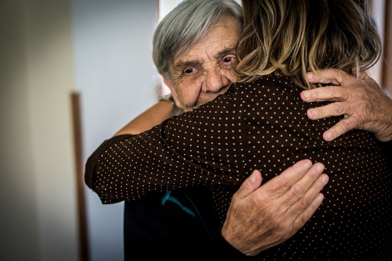 Elderly woman hugging another woman