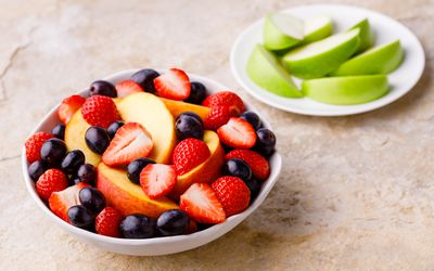 Bowl of apples, peaches, strawberries, and grapes
