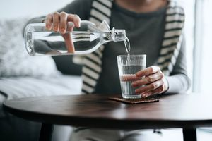 A woman pours bottled water into a drinking glass.