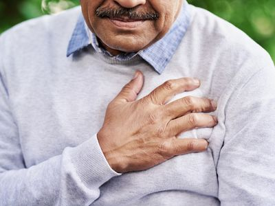 Older man with chest pain holding his chest with his hand