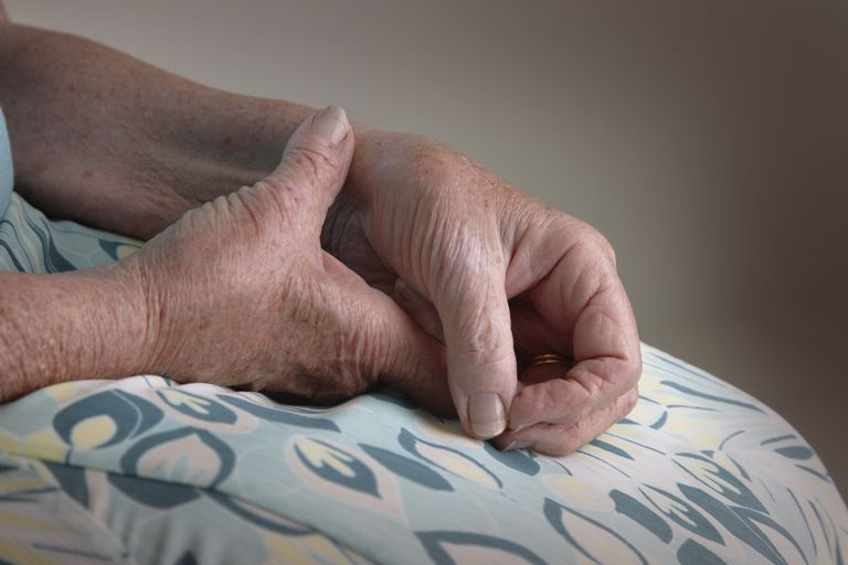an elderly woman holding her wrist