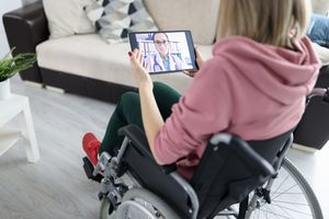 woman in wheelchair holding tablet for telehealth visit with doctor