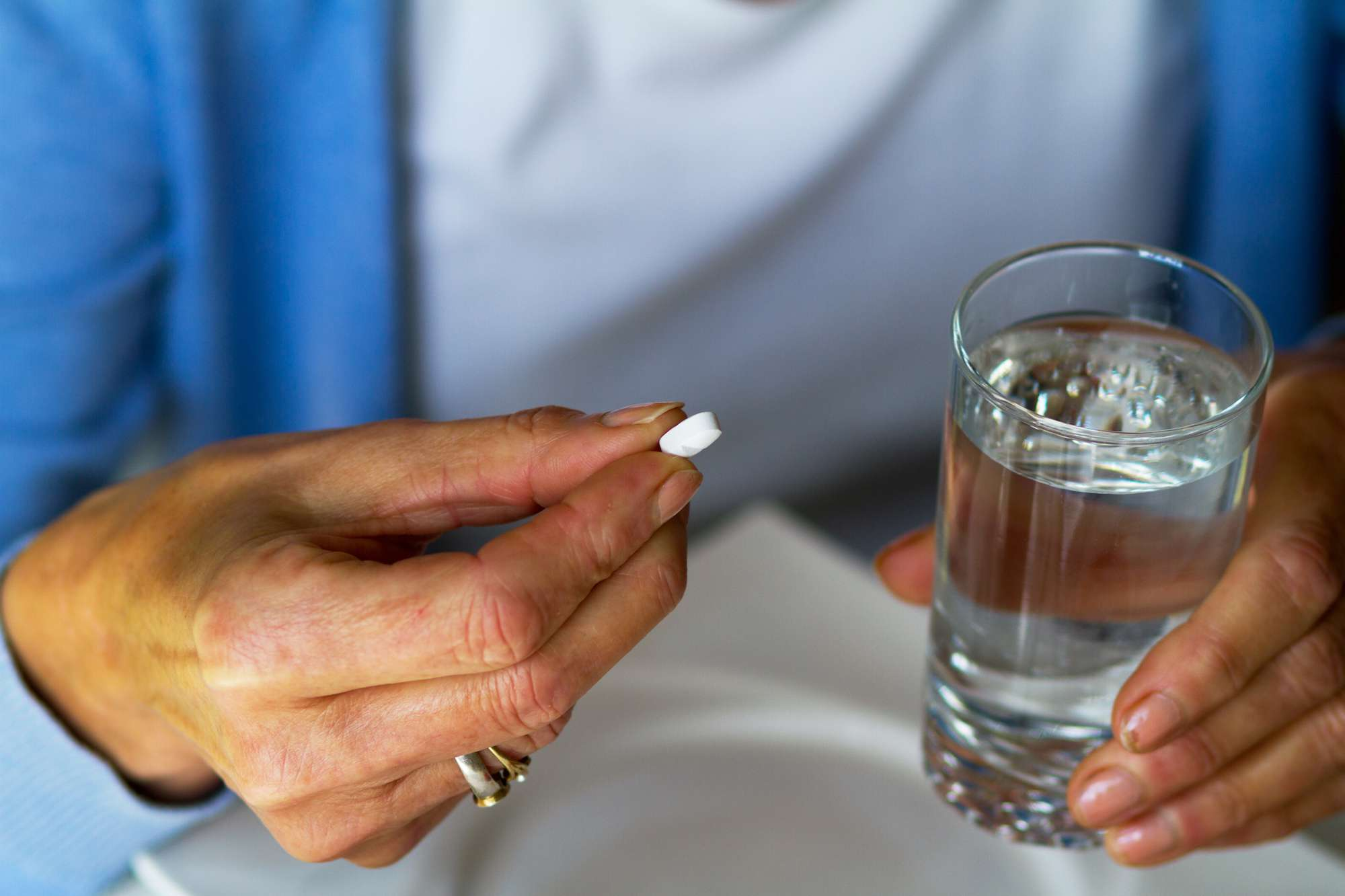 Close up of a woman's hands holding a pill and a glass of water